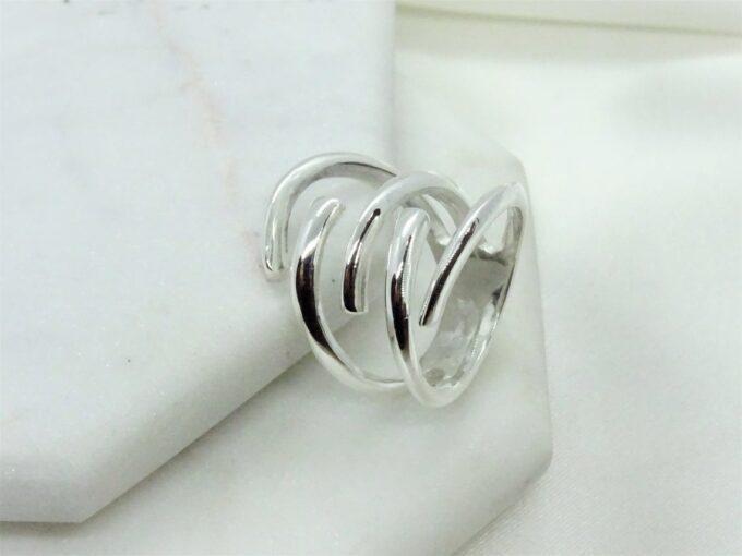 Нежен сребърен спираловиден пръстен, обвиващ пръста.